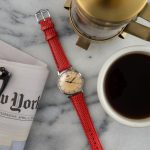 Flat lay photography for 15 hours Vintage watches. Scene: vintage watch with red band on marble counter top surrounded by folded New York Times newspaper, cup of coffee and coffee press.